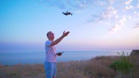 Το Quadrocopter πετά πέρα από το κεφάλι και τα εδάφη ατόμων ` s σε ετοιμότητα του Σε αργή κίνηση 4k φιλμ μικρού μήκους