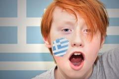 Το Redhead αγόρι ανεμιστήρων με την ελληνική σημαία χρωμάτισε στο πρόσωπό του Στοκ Εικόνα