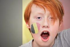 Το Redhead αγόρι ανεμιστήρων με τη βελγική σημαία χρωμάτισε στο πρόσωπό του Στοκ Φωτογραφία