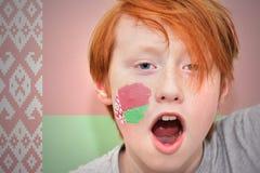 Το Redhead αγόρι ανεμιστήρων με τη λευκορωσική σημαία χρωμάτισε στο πρόσωπό του Στοκ φωτογραφία με δικαίωμα ελεύθερης χρήσης