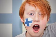 Το Redhead αγόρι ανεμιστήρων με τη φινλανδική σημαία χρωμάτισε στο πρόσωπό του Στοκ φωτογραφία με δικαίωμα ελεύθερης χρήσης
