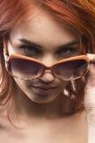 Το redhead κορίτσι στον τύπο 11 γυαλιών ηλίου Στοκ Φωτογραφία
