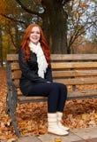 Το Redhead κορίτσι στο πάρκο πόλεων φθινοπώρου, κάθεται στον ξύλινο πάγκο, άνθρωποι ένας Στοκ Φωτογραφίες