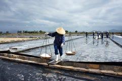 Το Saltworker φέρνει το άλας με το ζυγό ώμων στην αλυκή Στοκ Φωτογραφία