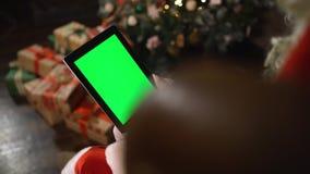 Το Santa επιλέγει τα δώρα σε IPad Ταμπλέτα με την πράσινη οθόνη απόθεμα βίντεο