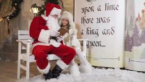 Το Santa διαβάζει τη συνεδρίαση μικρών κοριτσιών παραμυθιού κοντά σε ένα μαγικό βιβλίο απόθεμα βίντεο