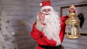 Το Santa κρατά ένα χρυσό φανάρι Χριστουγέννων Στοκ Εικόνες