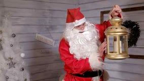 Το Santa κρατά ένα χρυσό φανάρι Χριστουγέννων Στοκ εικόνες με δικαίωμα ελεύθερης χρήσης
