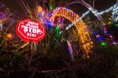 Το Santa παρακαλώ σταματά εδώ την κόκκινη ελαφριά διακόσμηση σημαδιών και Χριστουγέννων στοκ εικόνες