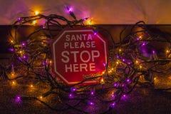 Το Santa παρακαλώ σταματά εδώ τα φω'τα σημαδιών και Χριστουγέννων στοκ εικόνες