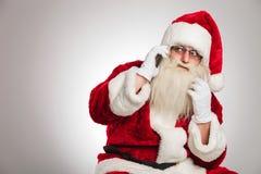 Το Santa που μιλά στο τηλέφωνο κοιτάζει στην πλευρά Στοκ Φωτογραφία