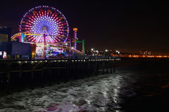Το Santa Monica Pier τη νύχτα με τα κύματα στο πρώτο πλάνο Στοκ Φωτογραφίες