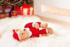 Το Santa tedyy αντέχει το παιχνίδι βρίσκεται sheepskin πλησίον στα φωτισμένα Χριστούγεννα Στοκ Φωτογραφίες