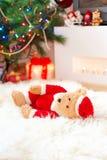Το Santa tedyy αντέχει το παιχνίδι βρίσκεται sheepskin πλησίον στα φωτισμένα Χριστούγεννα Στοκ εικόνα με δικαίωμα ελεύθερης χρήσης