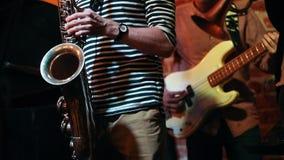 Το Saxophonist και ο κιθαρίστας παίζουν masterly σε μια απόδοση σε έναν φραγμό τζαζ απόθεμα βίντεο