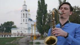 Το Saxophonist παίζει τη σάλπιγγα Ανάχωμα πόλεων το άτομο με το α επάνω mustache παίζοντας ένα μουσικό όργανο απόθεμα βίντεο