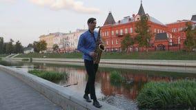 Το Saxophonist παίζει τη σάλπιγγα Ανάχωμα πόλεων το άτομο με το α επάνω mustache παίζοντας ένα μουσικό όργανο φιλμ μικρού μήκους