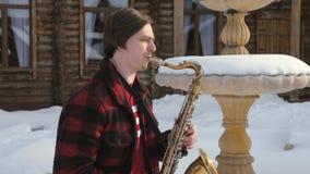 Το Saxophonist παίζει το saxophone, το χειμώνα απόθεμα βίντεο