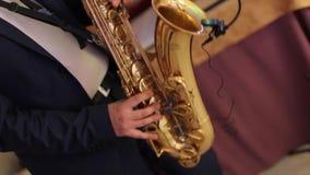 Το Saxophonist σε ένα σμόκιν παίζει τη μουσική στο σκεπάρνι Ο μουσικός παίζει την απόδοση saxophone σε μια συναυλία Νύχτα της Jaz απόθεμα βίντεο