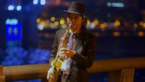 Το saxophonist στη νύχτα περιπάτων παίζει την τζαζ φιλμ μικρού μήκους