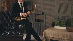 Το Saxophonist στο σακάκι γευμάτων κάθεται στην καρέκλα με το χρυσό saxophone Μουσικός της Jazz φιλμ μικρού μήκους