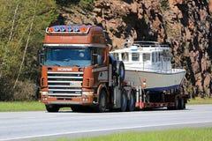 Το Scania 144 μεταφέρει μια ψυχαγωγική βάρκα κατά μήκος της εθνικής οδού Στοκ φωτογραφία με δικαίωμα ελεύθερης χρήσης