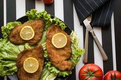 Το Schnitzel εξυπηρετεί με τα πράσινα και το λεμόνι Στοκ Εικόνες