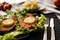 Το Schnitzel εξυπηρετεί με τα πράσινα και το λεμόνι Στοκ φωτογραφίες με δικαίωμα ελεύθερης χρήσης