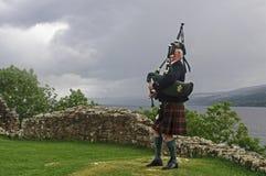 Το Scot παίζει bagpipes μπροστά από το Λοχ Νες στοκ φωτογραφία με δικαίωμα ελεύθερης χρήσης