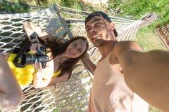 Το Selfie ενός νέου ζεύγους, το κορίτσι βρίσκεται σε μια αιώρα με τη κάμερα, ο τύπος στέκεται δίπλα στην κλίση Στοκ Εικόνα
