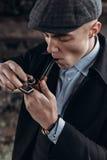 Το Sherlock holmes κοιτάζει, άτομο στην αναδρομική εξάρτηση, κάπνισμα, που ανάβει τον ξύλινο σωλήνα θέμα της Αγγλίας το 1920 s μο Στοκ Εικόνες