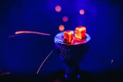 Το Shisha hookah με τις καμμένος κόκκινες χοβόλεις και πέταγμα σπινθηρίζει στο κύπελλο στο μπλε υπόβαθρο Στοκ Εικόνες