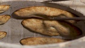 Το shoti ψωμιού ψήνει στον παραδοσιακό φούρνο αργίλου φιλμ μικρού μήκους