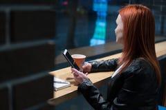 Το smartphone εκμετάλλευσης κοριτσιών υπό εξέταση, κάθεται στον καφέ, εργασία, μάνδρα, συσκευή χρήσης Δίκτυο, wifi, κοινωνικό, επ στοκ φωτογραφίες
