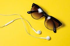 Το Smartphone με την κενή οθόνη συνδέει με τα ακουστικά με το σπειροειδές καλώδιο στην κίτρινη τοπ άποψη υποβάθρου, γυαλιά ηλίου στοκ εικόνες