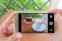 Το Smartphone παίρνει τη φωτογραφία του καφέ και του κέικ Στοκ φωτογραφία με δικαίωμα ελεύθερης χρήσης