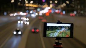 Το smartphone τοποθετείται σε ένα τρίποδο Παίρνουν τις εικόνες της μετακίνησης των αυτοκινήτων, στο υπόβαθρο των όμορφων φω'των απόθεμα βίντεο