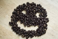 Το smiley διαμορφώνεται από τα φασόλια καφέ σε ένα ελαφρύ ξύλινο υπόβαθρο στοκ εικόνες