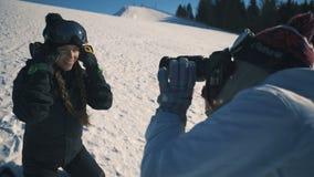 Το Snowboarder ή ο σκιέρ και ο φωτογράφος κάνουν τη σύνοδο φωτογραφιών για το χιονοδρομικό κέντρο το μέσο πυροβολισμό φιλμ μικρού μήκους