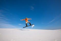 Το Snowboarder πετά πέρα από τον αμμόλοφο άμμου Στοκ Εικόνες