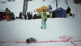 Το Snowboarder ρίχνει το παπούτσι στην απόσταση στην κλίση στο χιονώδες ίχνος, που αποκτάται στο κορίτσι με τη κάμερα ανταγωνισμό φιλμ μικρού μήκους