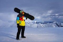 Το Snowboarder φέρνει ένα σνόουμπορντ υπό εξέταση Στοκ φωτογραφία με δικαίωμα ελεύθερης χρήσης