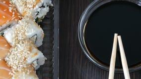 Το Stylishly έβαλε τα σούσια που τέθηκαν σε ένα μαύρο ξύλινο υπόβαθρο δίπλα στη σάλτσα σόγιας και τα κινεζικά ραβδιά μπαμπού σούσ φιλμ μικρού μήκους