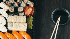 Το Stylishly έβαλε τα σούσια που τέθηκαν σε ένα μαύρο ξύλινο υπόβαθρο δίπλα στη σάλτσα σόγιας και τα κινεζικά ραβδιά μπαμπού σούσ απόθεμα βίντεο