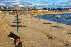 Το Sunshades είναι μια αμμώδης παραλία στο υπόβαθρο των δέντρων Στοκ Φωτογραφία