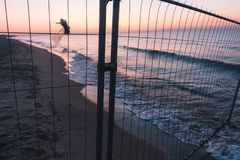 Το Sunsut στην παραλία στη θάλασσα ή ο ωκεανός πίσω από το πλέγμα περιφράζει Στοκ Εικόνες