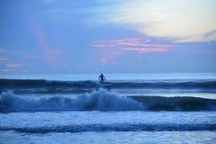 Το surfer απογειώνεται σε έναν μακροχρόνιο γύρο στην άμμο beachfront στοκ φωτογραφία