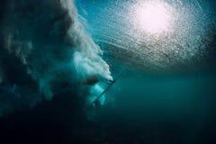 Το Surfer με την ιστιοσανίδα βουτά υποβρύχιος με το κατώτερο κύμα στοκ εικόνα