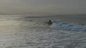Το Surfer οδηγά ένα κύμα στο πέρασμα απόθεμα βίντεο