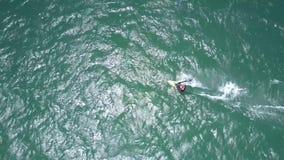 Το Surfer οδηγά τα κύματα και κάνει το foamy ίχνος φιλμ μικρού μήκους